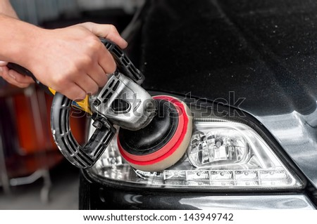 Car headlights cleaning with power buffer machine at car service - stock photo