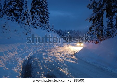 Car headlights in snowy night