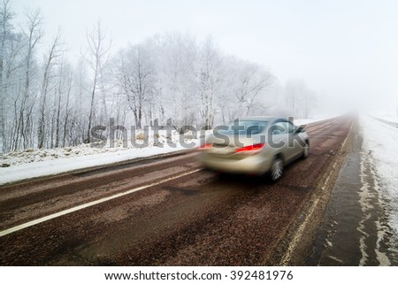 Car in high speed captured with blurry motion on wintry conditions