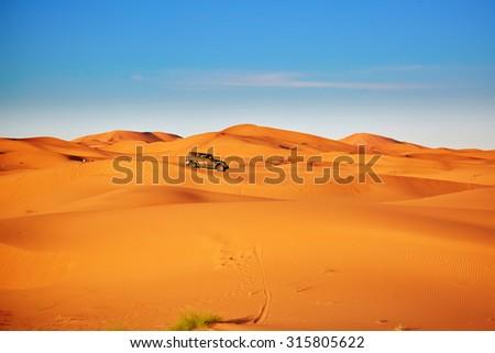 Car in sand dunes in the Sahara Desert, Merzouga, Morocco - stock photo