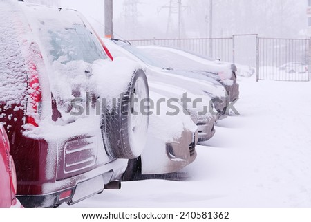 car in the parking lot under the snow - stock photo