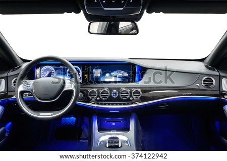 Car inside driver place. Interior of prestige modern car. Steering wheel, dashboard, display & climate control. Black cockpit with wood & metal decoration & ambient light on isolated white background. - stock photo