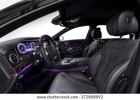 Car inside driver seat. Interior of prestige modern car. Front seat with display,steering wheel & dashboard. Black cockpit wood & metal decoration & violet ambient light on isolated white background. - stock photo
