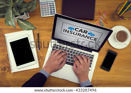 CAR INSURANCE Close up of business man hand working  laptop computer on wooden desk - stock photo