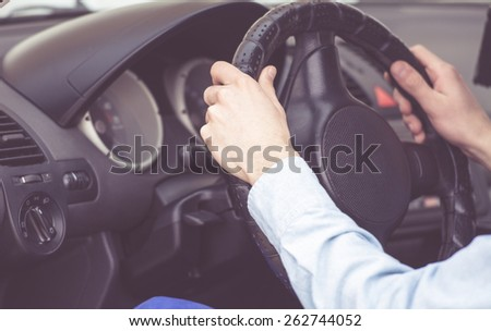 car interior with a person holding the steering wheel