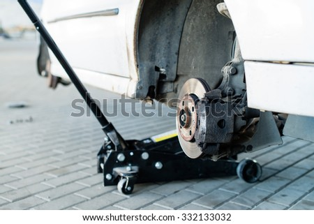 car jack to lift for tire (shallow DOF) - stock photo