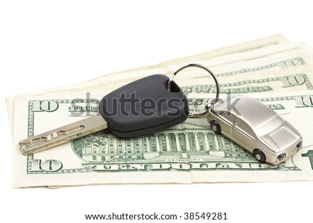 Car key and dollar bills on white background with shallow depth of field - stock photo