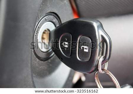 car key inserted into the lock of ignition of the car - stock photo