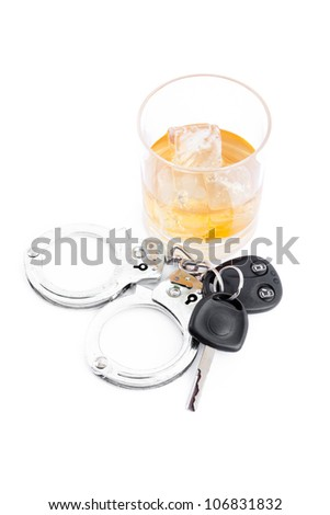 Car key next to a whiskey and a handcuff against a white background - stock photo