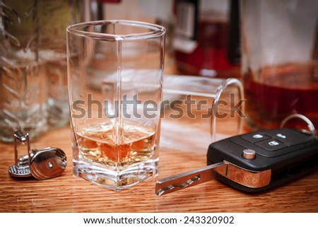 Car key on the bar with spilled alcohol and empty bottles. Booze driving concept. Drunk driver concept - stock photo