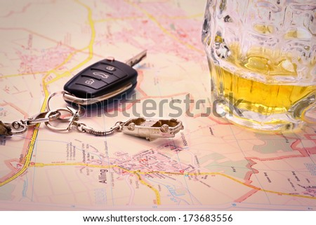 Car key with accident and beer mug on map, close up