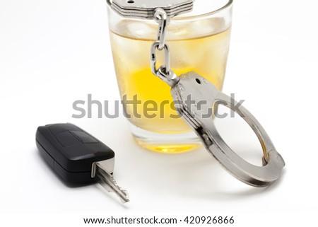 Car key with glass of whiskey and handcuffs - drive under influence concept - stock photo