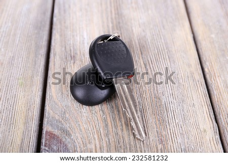 Car key with remote control on wooden table, close-up - stock photo