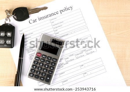Car keys on insurance documents, close up - stock photo