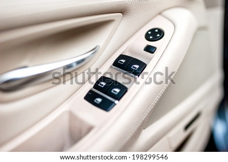 car leather interior details of door handle with windows controls and adjustments. Car window controls  - stock photo