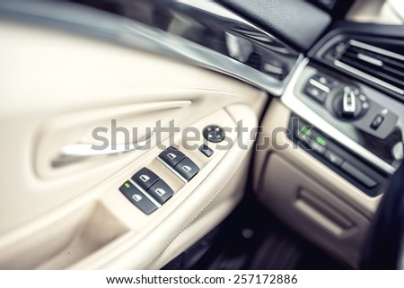 car leather interior details of door handle with windows controls and adjustments. Car window controls of modern car - stock photo