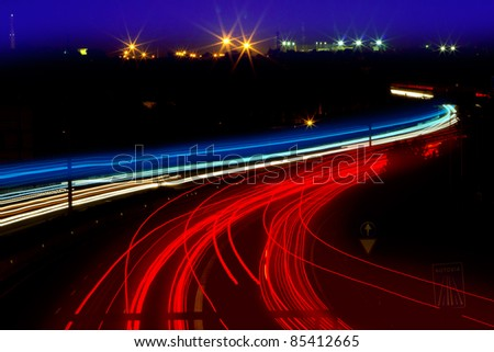 car light trails in red and white on night road curve - stock photo
