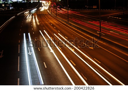 Car light trails on a freeway at night - stock photo