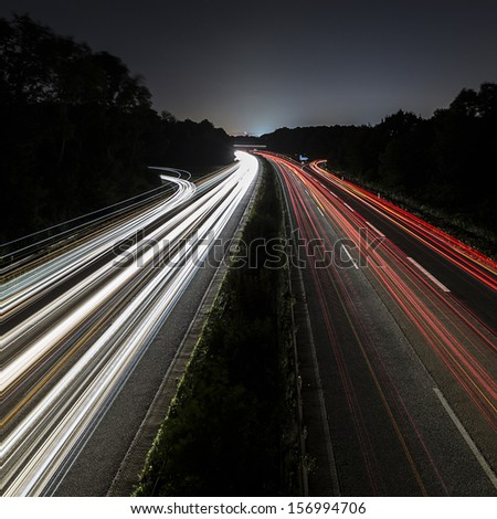 Car light trails on highway at night - stock photo