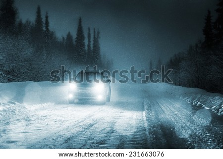 Car lights in winter forest - stock photo