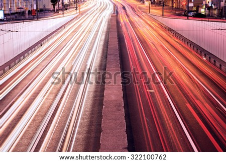 Car lights on the central city streets at evening time. - stock photo