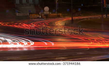 Car lights on the central city streets at evening time longexposure - stock photo