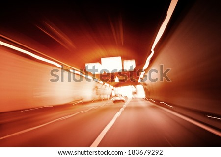Car lights trails in a tunnel - stock photo