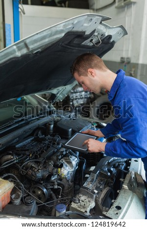 Car mechanic by car using tablet computer - stock photo