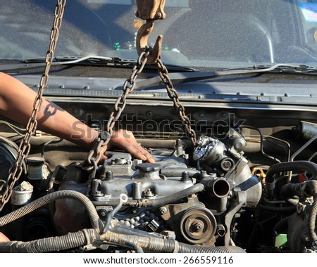 Car mechanic changing engine of the old car - stock photo