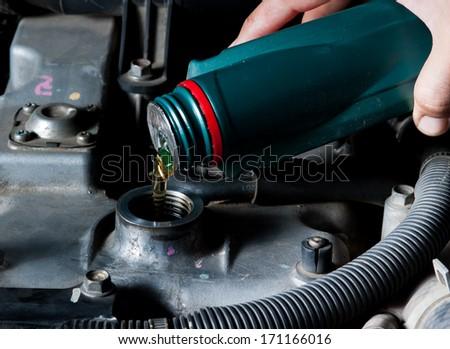 Car mechanic changing engine oil - stock photo