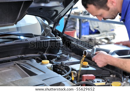 Car mechanic changing oil - model and oil motion blurred. - stock photo