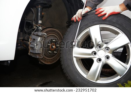 Car mechanic changing tire in professional car repair service - stock photo