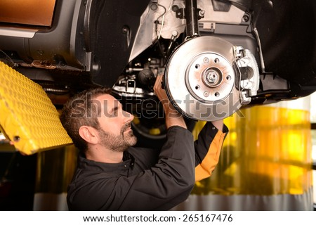 Car mechanic checking car at auto repair shop service station, front or rear axle inspection - stock photo