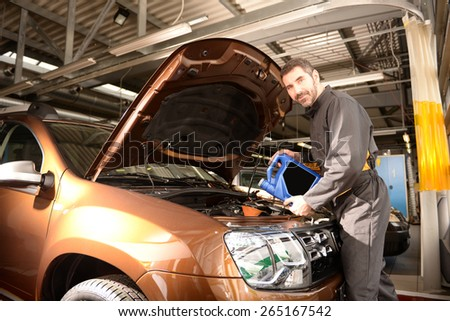 Car mechanic checking car at auto repair shop service station, oil inspection and refill