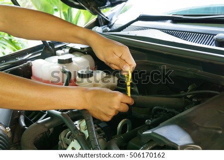 Car mechanic checking oil.