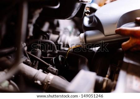 Car mechanic fills engine oil - stock photo
