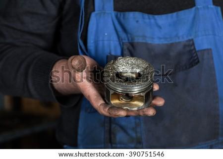 Car mechanic hand with damaged engine valve piston at repair service. Garage concept - stock photo