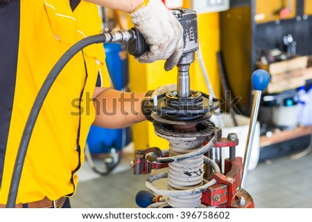 Car mechanic hands inspecting a shock absorber in vise at repair service. Garage room