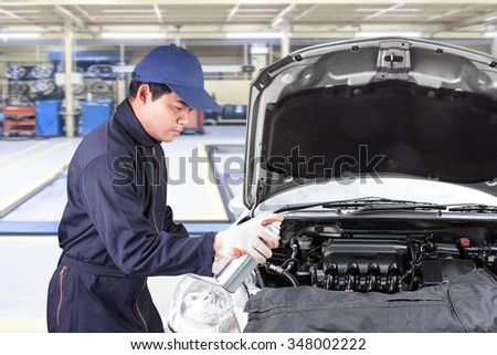 Car mechanic holding aerosol cans spray oil into engine at maintenance repair service station  - stock photo
