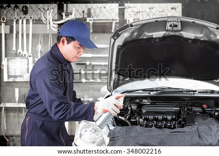 Car mechanic holding aerosol cans spray oil into engine at maintenance repair service station with tools background - stock photo