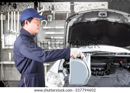 Car mechanic holding gray canister with engine oil for replacing and pouring oil into engine at maintenance repair service station with tools background - stock photo