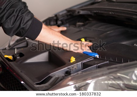 Car mechanic in his repair shop standing next to the car, close-up of the engine