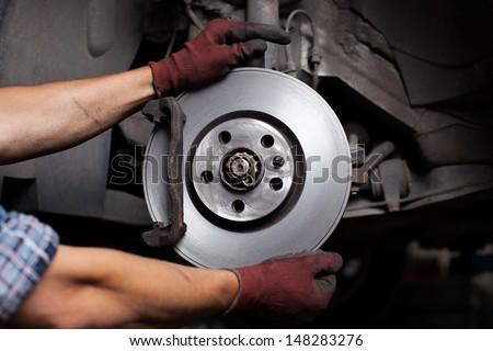 Car mechanic Repairing brakes on car - stock photo