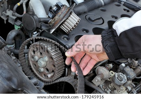 Car mechanic replacing timing belt at camshaft of modern engine - stock photo