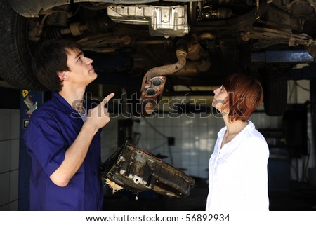 car mechanic talking to costumer at the car  repair  shop - stock photo