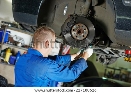 car mechanic worker repairing suspension of lifted automobile at auto repair garage shop station - stock photo