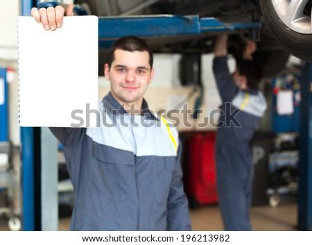 Car mechanic working in auto repair service. - stock photo