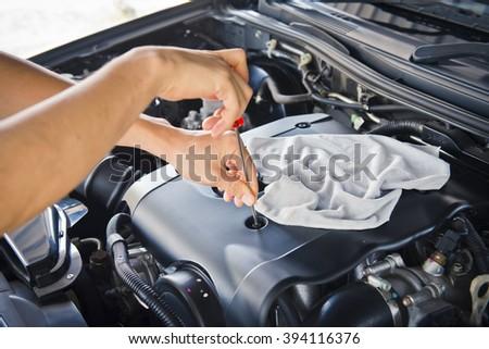 Car mechanic working in the repair garage ,mechanic checking under hood  - stock photo