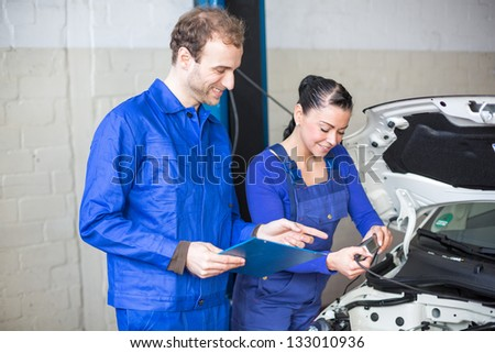 Car mechanics repairing car electrics and other parts of the motor