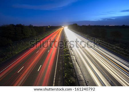 car motorway trails at dusk - stock photo